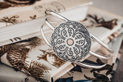 Silver bangle bracelet with ethnic ornament on rustic background