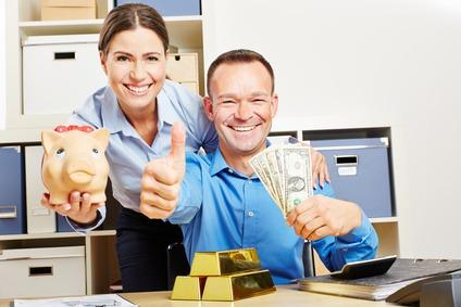 Glückliches Paar mit Geld in Dollar und Gold als Goldbarren hält Daumen hoch